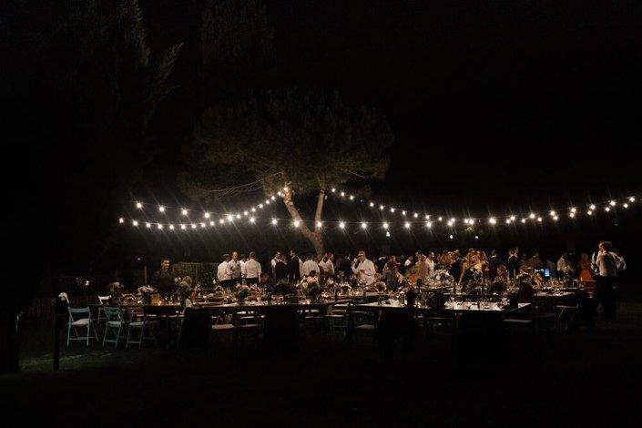 Hochzeitsfotografie Barcelona - Diese Bild ist auf einer Hochzeit in der Nähe von Barcelona entstanden. - Es zeigt einen warmen Sommerabend - Eine Lichterkette hängt über den wunderschön gedeckten Tischen- Die Gäste sind in Aufbruch Stimmung. Es ist schon Nacht und nur die Lichterketten lassen die Szenerie erleuchten.