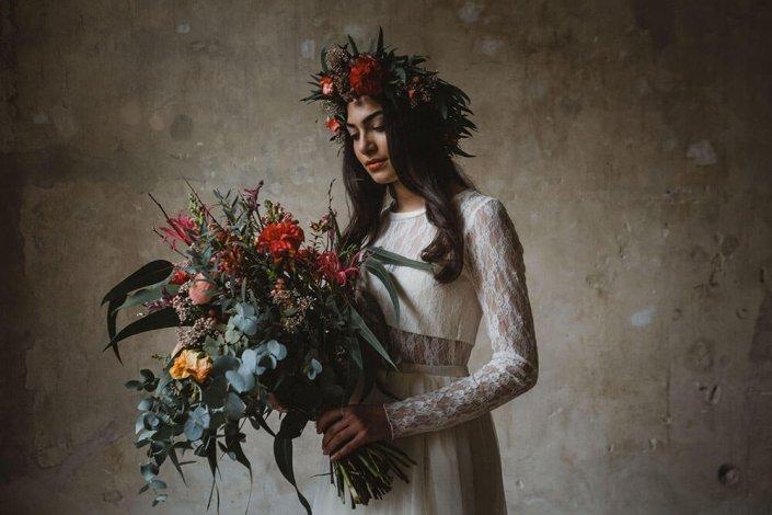 Brautmode aus Hamburg- Nahaufnahme Model - Das Model schaut auf den großen Blumenstrauß- Das Bild entstand im Haller6.- Eine großartige Fotolocation im Herzen von Hamburg.