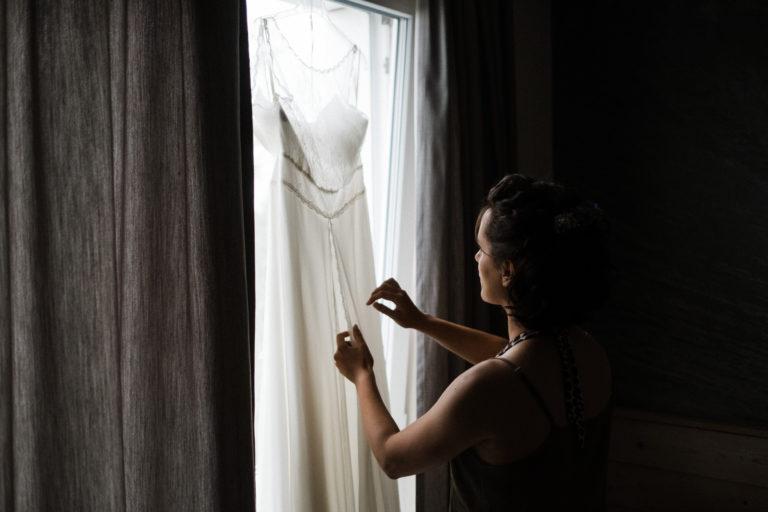 Hochzeitsfotografie Sankt-Peter-Ording- Getting Ready Beach Motel- Braut schaut sich die Details ihres Brautkleides an.