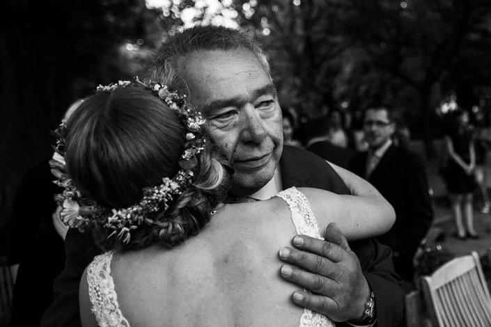 Hochzeitsfotografie Hamburg. Reportagebild der Gratulation. Der Brautvater nimmt seine Tochter in den Arm und ist zu Tränen gerührt.