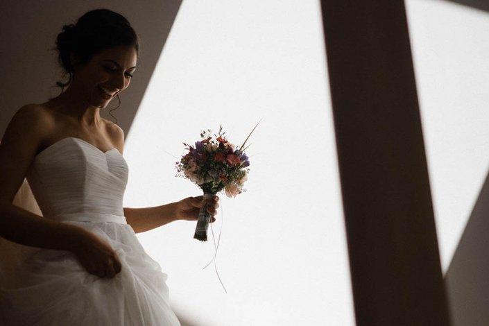 Braut mit Brautstrauß. Sie geht durch einen Lichtfleck nur der Brautstrauß wird dadurch in Szene gesetzt.