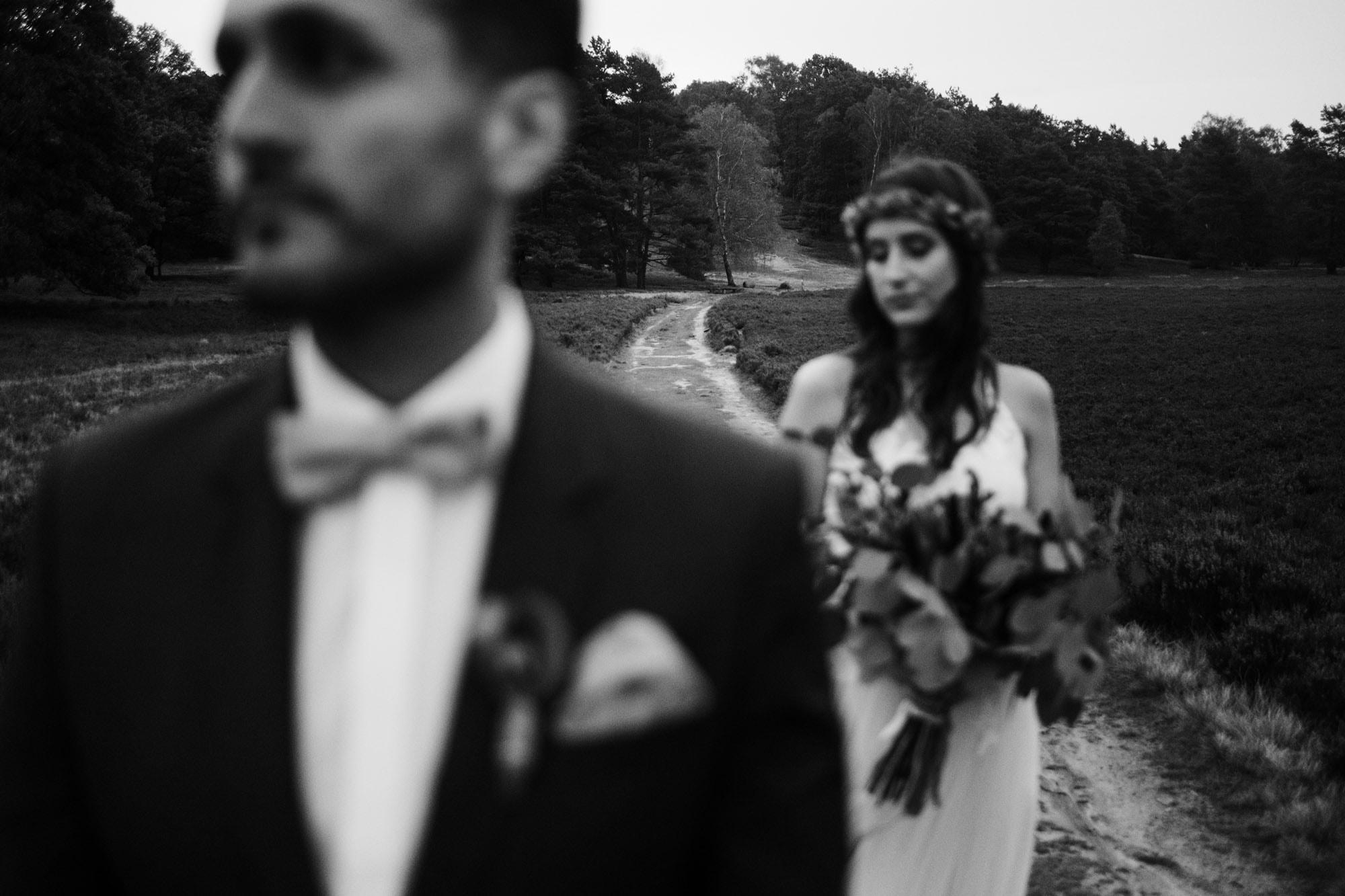Brautpaar steht hintereinander, inmitten einer Weges in der Fischbeker Heide. Der Fokus des Bildes liegt auf dem Weg.