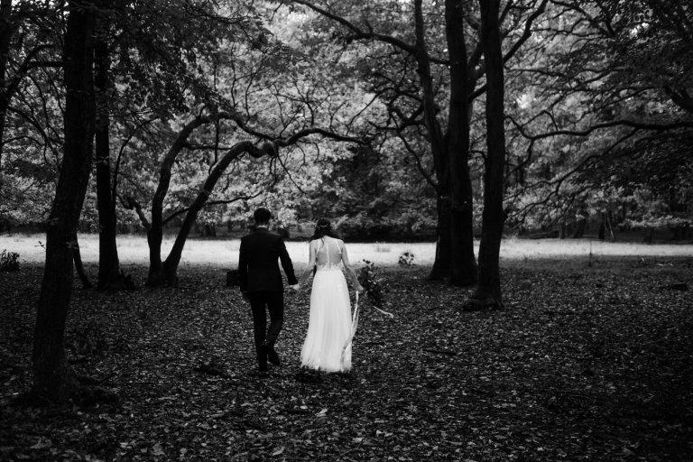 After-Wedding-Session-Hamburg- Brautpaar läuft durch den Wald in Richtung Lichtung