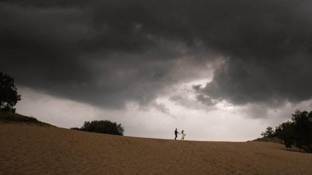 Hochzeitsfotografie Hamburg- Boberger Dünen- Brautpaar geht Hand in Hand die Dünen entlang. Über Ihnen eine dicke Gewitterwolke.