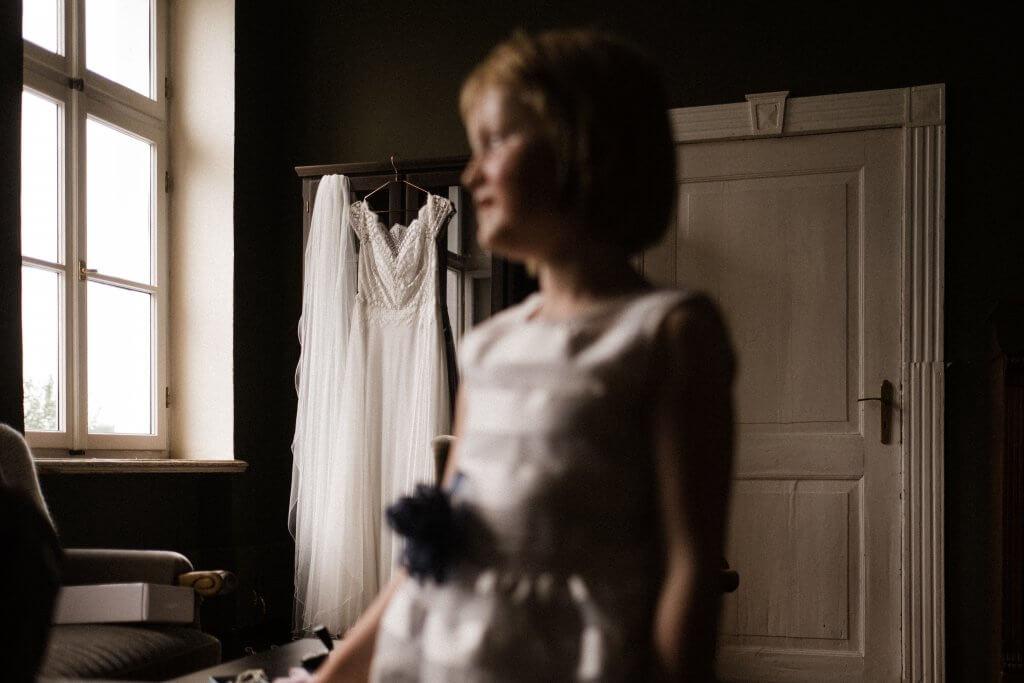 Frau-Siemers. Hochzeitsfotografie Hamburg. Im Vordergrund steht ein Kind unscharf, im Hintergrund ist ein Vintage Brautkleid scharf dargestellt.