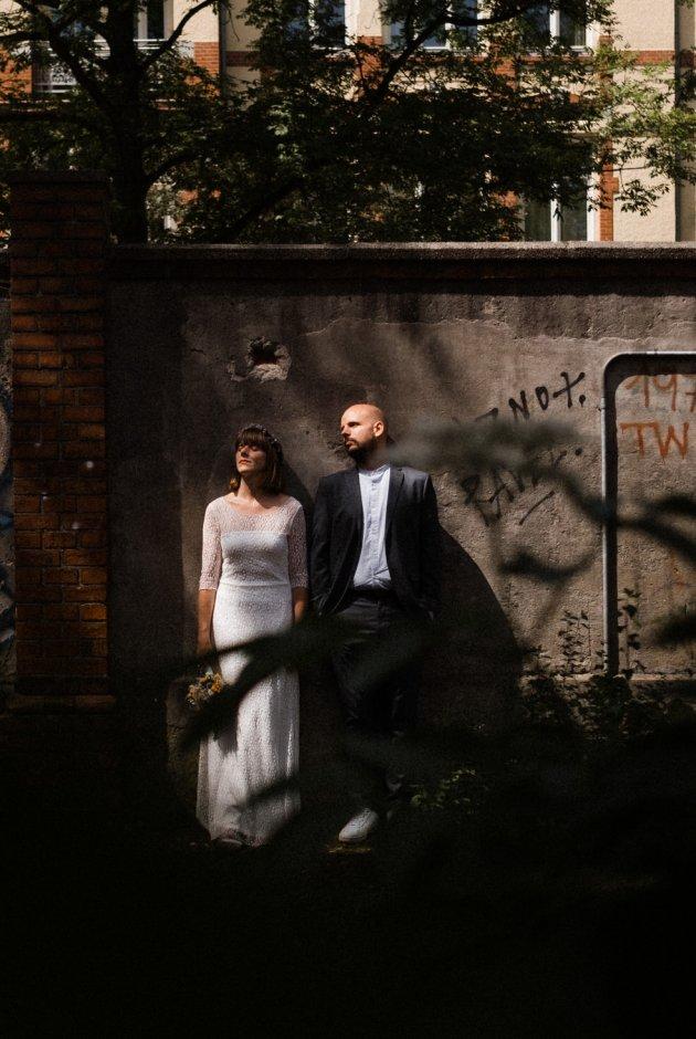 Portrait eines Brautpaares, dass an einer Wand lehnt. Das Brautpaar lässt di Sonnenstrahlen auf ihr Gesicht scheinen.