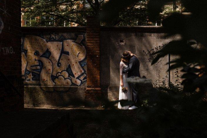 Brautpaar küsst sich vor einer Graffiti Wand.