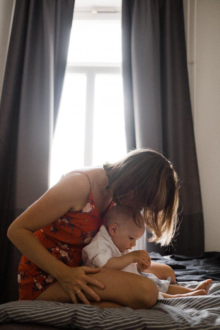 Braut kuschelt mit ihrem Kind auf dem Bett sitzend.