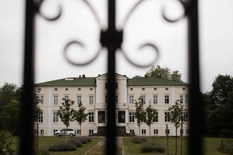 im Vordergrund ist ein Metalltor zu sehen, hinter dem Tor ist eine große Villa