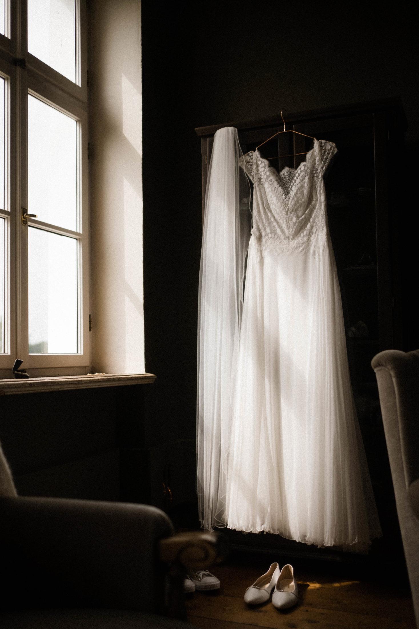 Hochzeitsfotografie La Dersentina. Das Brautkleid höngt an einem Kleiderbügel am Fenster in der Villa, der Schleier hängt daneben, die Brautschuhe stehen davor auf dem Boden, die Sonne scheint in das Fenster