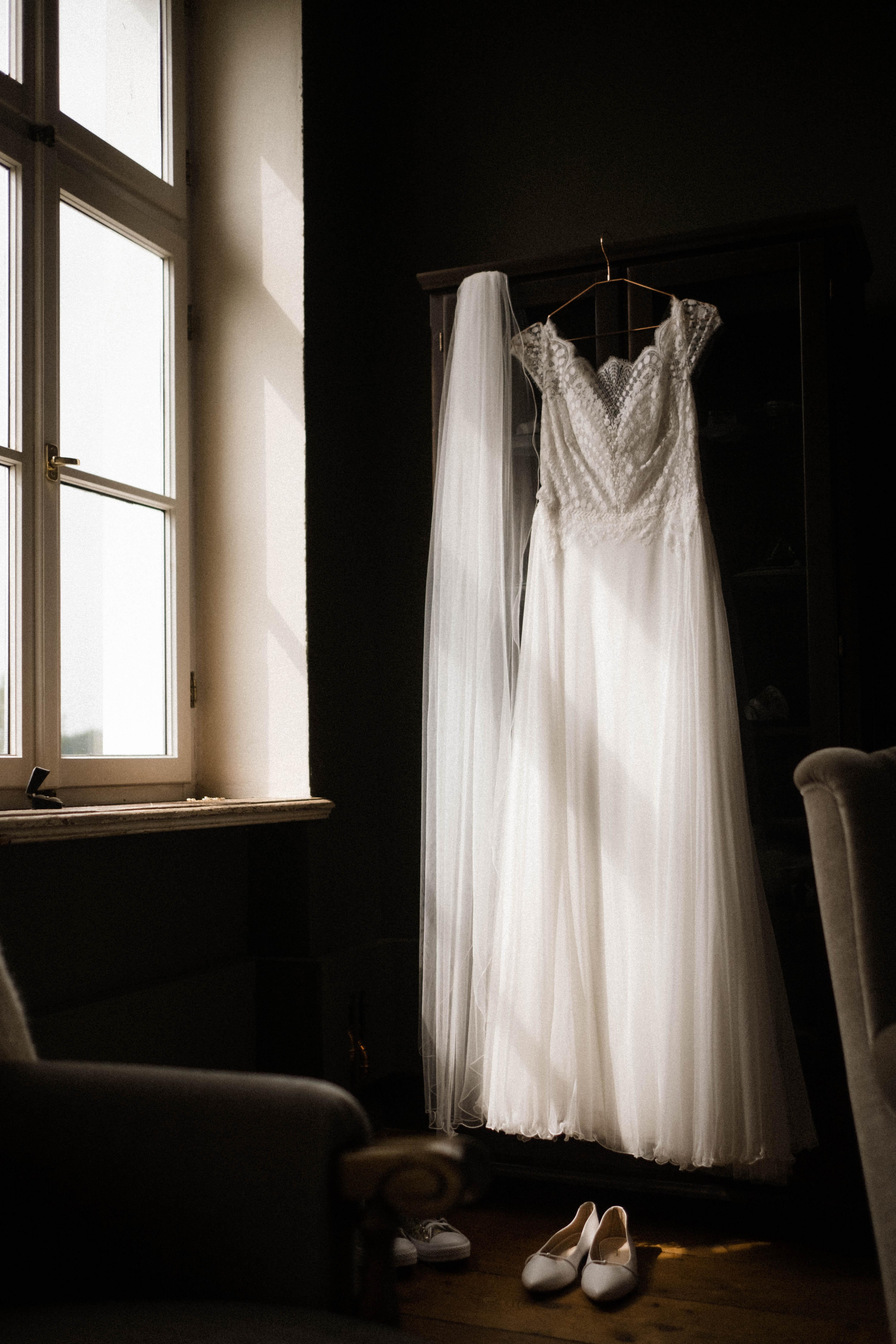 das Brautkleid höngt an einem Kleiderbügel am Fenster in der Villa, der Schleier hängt daneben, die Brautschuhe stehen davor auf dem Boden, die Sonne scheint in das Fenster