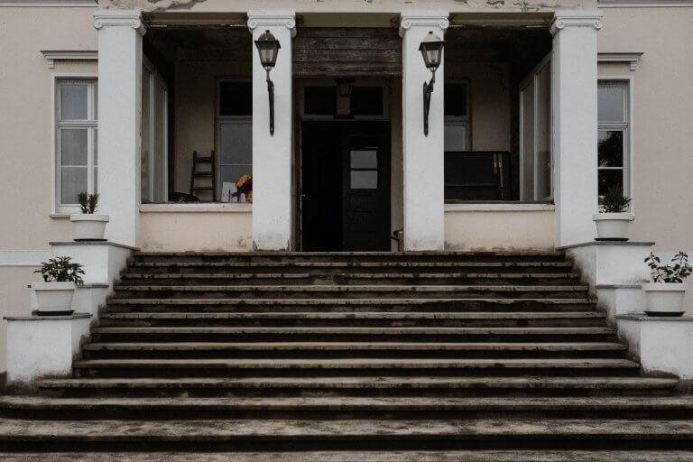 Eine breite Treppe führt zu dem Eingang der Villa