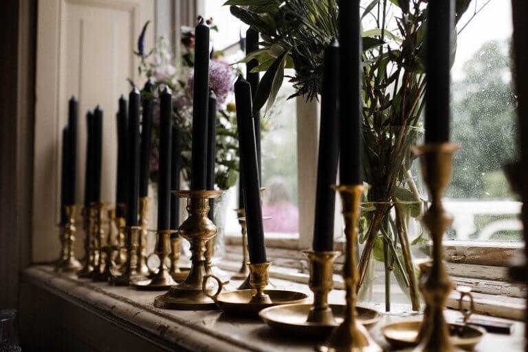 auf der Fensterbank in der Villa stehen goldene Kerzenhalter mit grünen Stabkerzen, dahinter stehen sind Blumenvasen