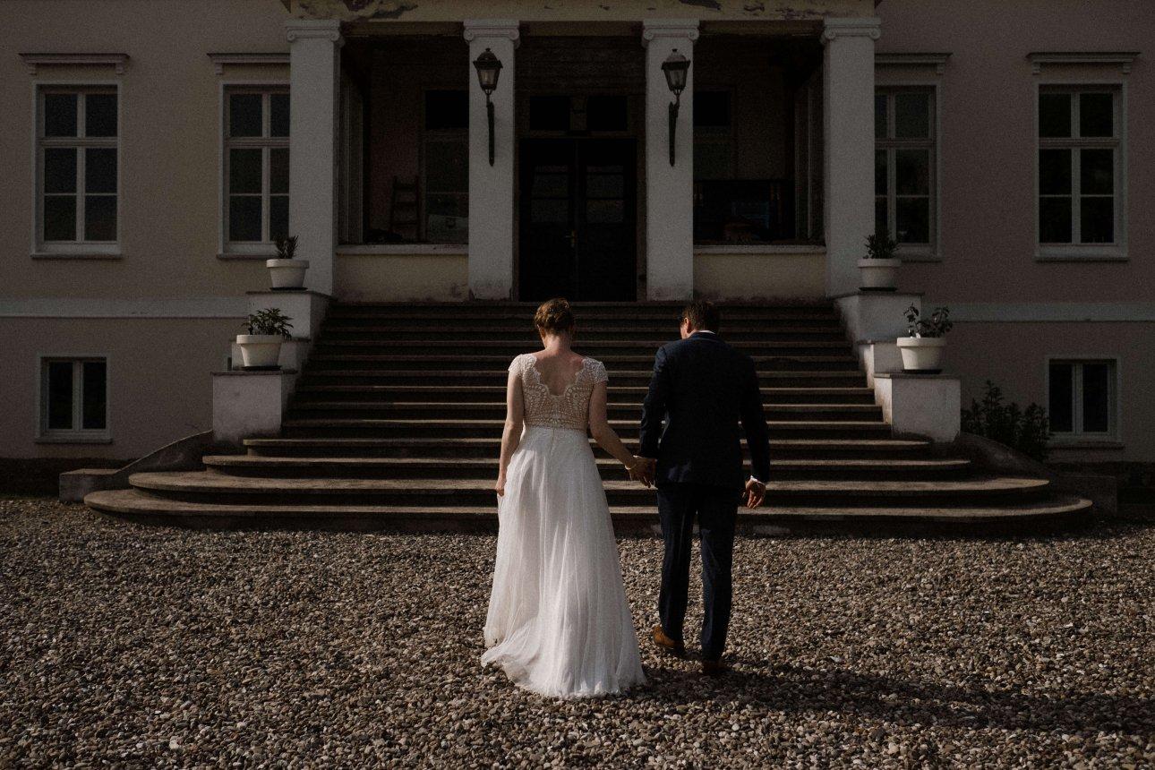 Das Brautpaar steht Hand in Hand vor der Treppe , die zur Tür der Villa führt