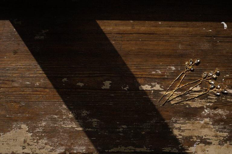 auf einem alten Tisch in der Villa liegen 3 goldene Haarnadeln,