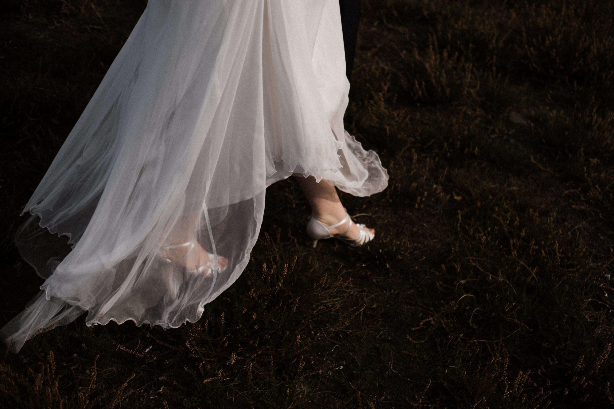 Braut geht über Moos, es sind auf dem Bild nur die Brautschuhe und ein Teil der Rockes zu sehen.