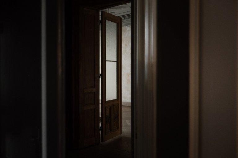 eine Holztür steht auf in die Richtung eines weiteren Zimmers in Haller 6