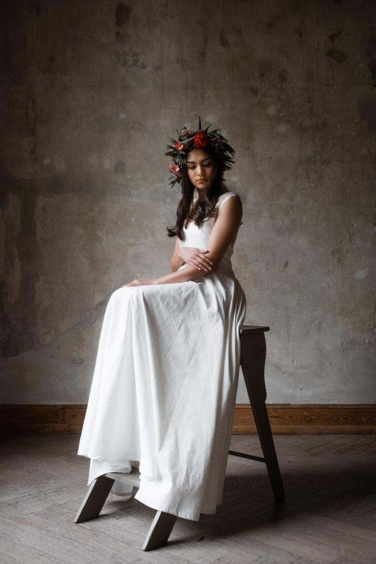 vor einer naturbelassenen Wand in Haller 6 steht eine kleine Holzleiter, auf der eine Frau in einem langen Brautkleid sitzt, sie trägt einen großen Haarkranz auf dem Kopf, sie schaut auf den Boden, ihre Arme sind verschränlt