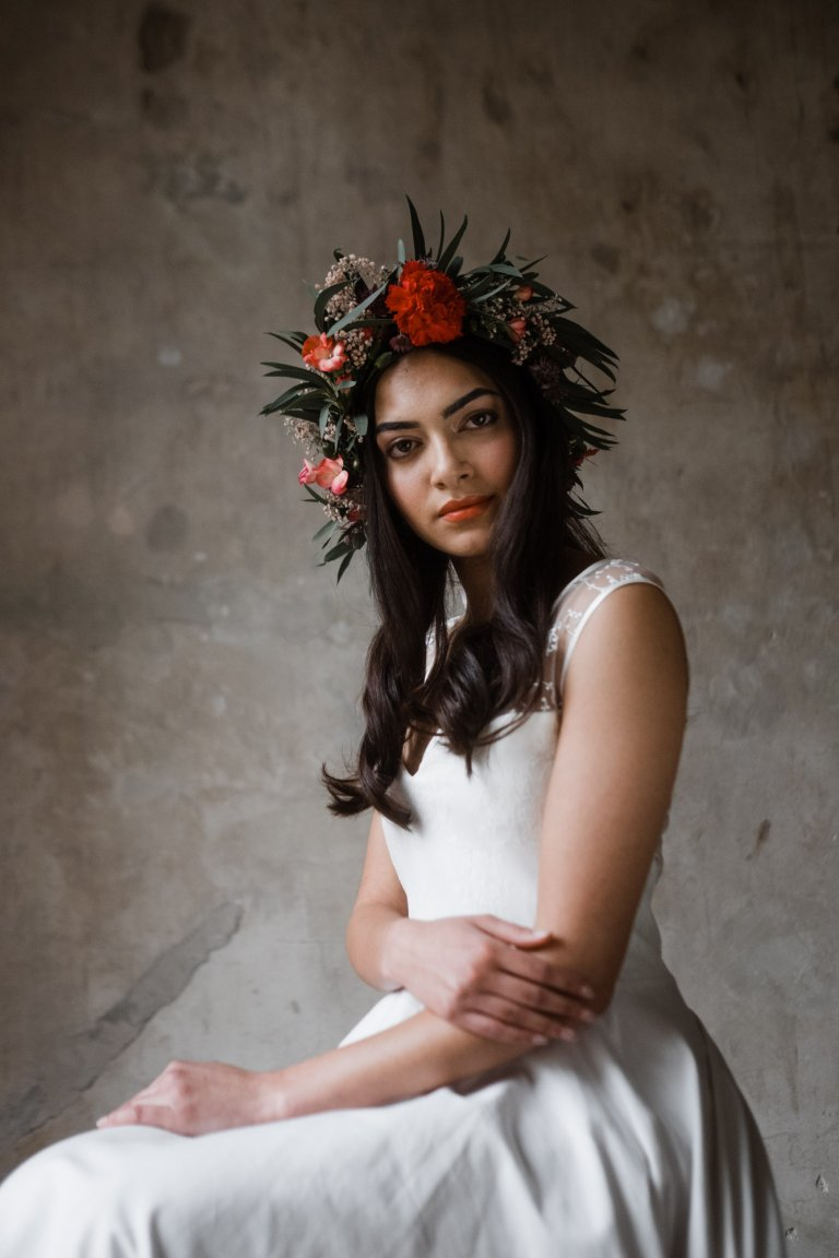 vor einer naturbelassenen Wand in Haller 6 sitzt eine Frau in einem Brautkleid, sie trägt einen großen Blumenkranz auf dem Kopf, sie schaut in die Kamera, ihre Arme hält sie verschränkt vor ihrem Bauch