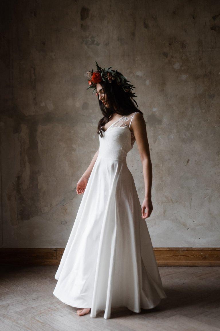 vor einer naturbelassenen Wand in Haller 6 steht eine Frau in einem langen Brautkleid, ihre Arme hängen herunter, sie schaut nach unten, sie dreht ihren Körper