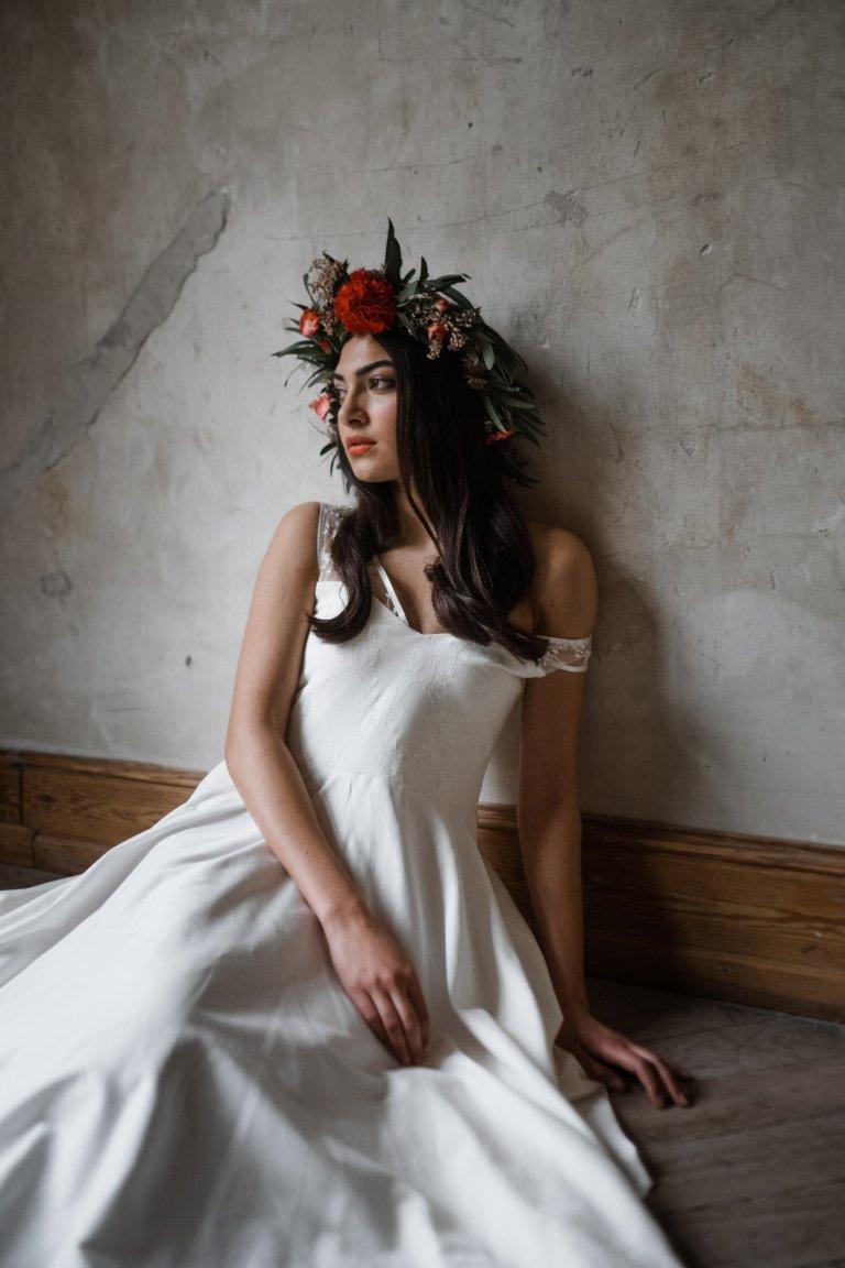 eine Frau sitzt in einem Zimmer auf dem Boden in Haller 6, ihr Kopf lehnt an der naturbelassenen Wand, sie trägt ein langes Brautkleid und einen großen Haarkranz auf dem Kopf, sie schaut in die Ferne