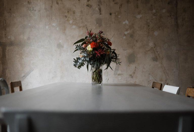 in dem Zimmer in Haller 6 steht ein Tisch, auf dem ein Blumenstrauß in einer Vase steht, die Wand dahinter hat eine naturbelassene Wandoberfläche