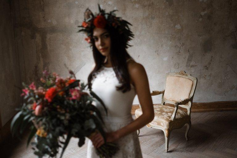 vor einer naturbelassenen Wand in Haller 6 steht ein antiker Sessel, im Vordergrund steht eine Frau in einem Brautkleid, sie hält einen üppigen Blumenstrauß in der Hand und sie trägt einen großen Blumenkranz auf dem Kopf