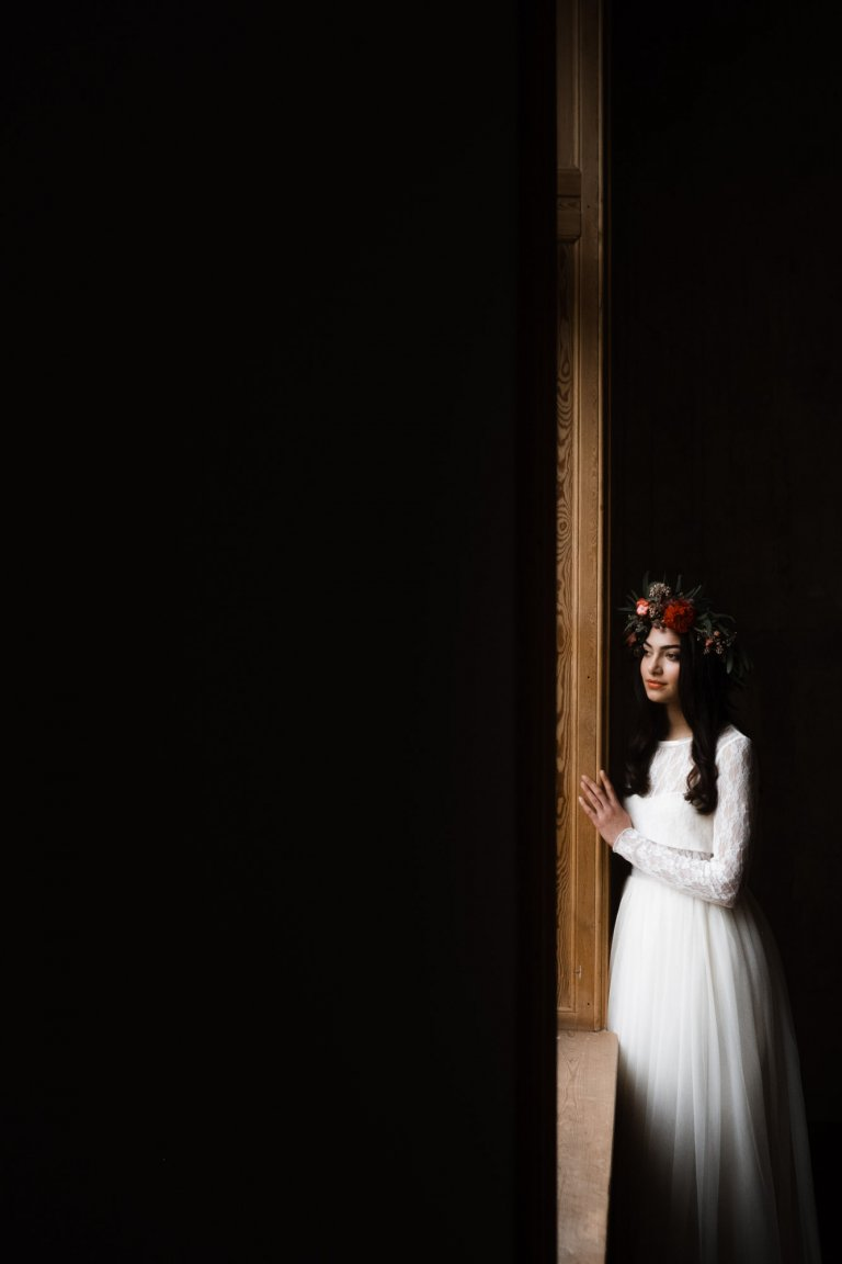 eine Frau im Brautkleid steht in Haller 6, sie lehnt an großen Holzfenster und schaut nch drußen