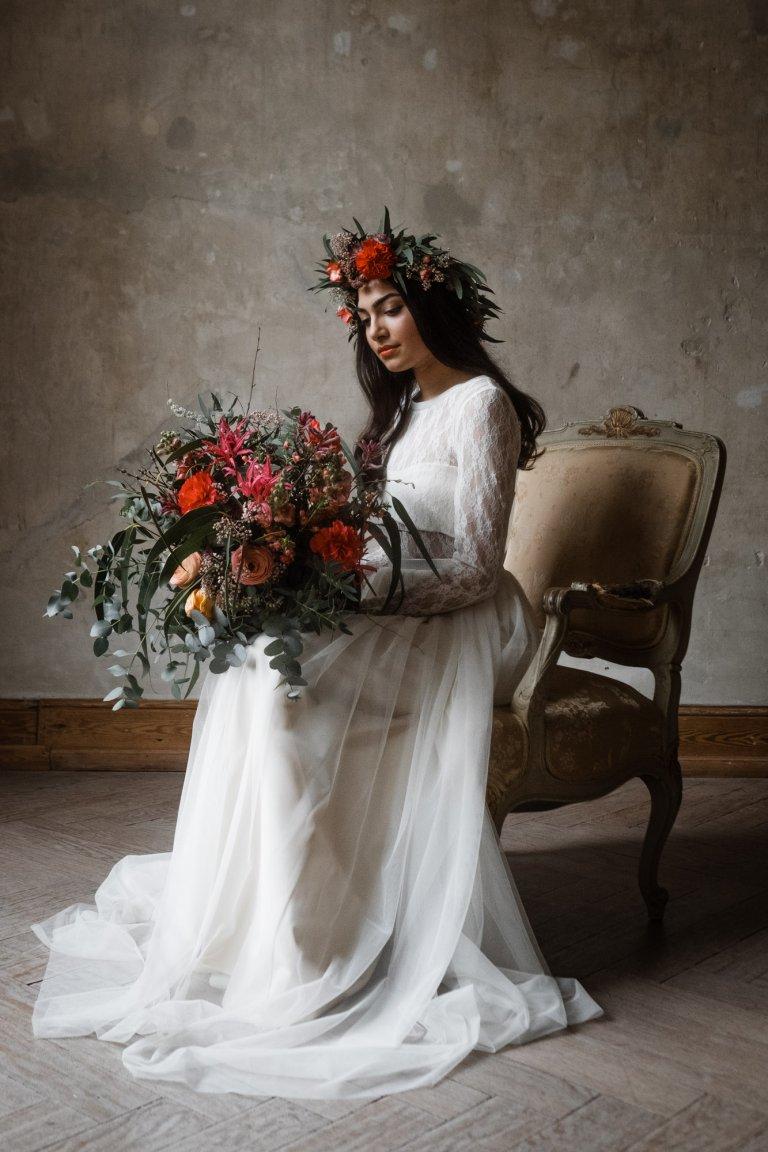 vor der naturbelassenen Wand steht ein antiker Sessel, auf dem Sessel sitzt eine Frau, die ein langes Brautkleid trägt, sie hält einen üppigen Blumenstrauß in der Hand und sie trägt einen Haarkranz aus Blumen