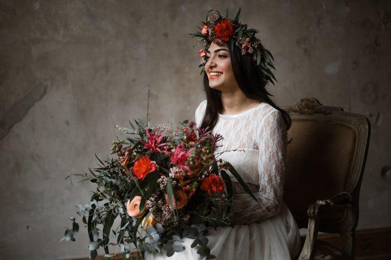 Titelbild der Portfolio-Seite zum Thema Hochzeitsfotografie. Braut in der Location Haller 6 fotografiert. Die Braut sitzt auf einem Stuhl und lacht. in der Hand hält sie einen Strauß im angesagten Boho-Look.
