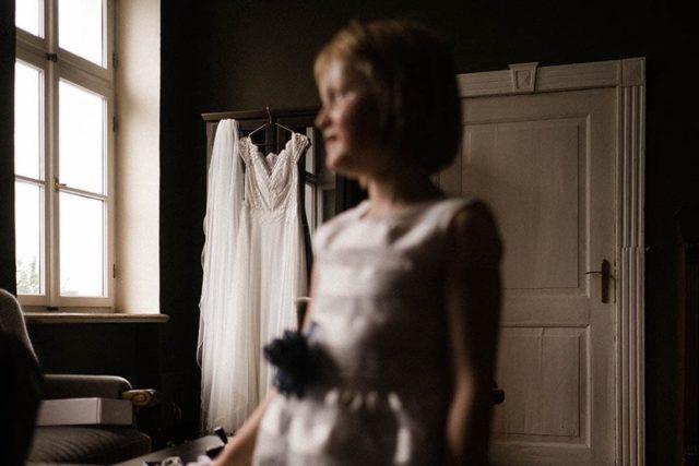 Frau-Siemers-Hochzeitsfotografie Hamburg- Reportagebild- Zu sehen ist im Vordergrund, unscharf gehalten, das Blumenkind. Im Hintergrund befindet sich, an einem Schrank hängend das Brautkleid. Das Bild wirkt durch den seitlichen Blick des Kindes sehr verträumt.