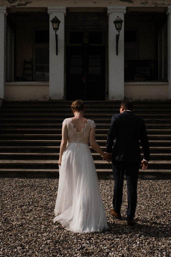 Hochzeitsfotografie Hamburg/Frau Siemers/Auf dem Bild ist ein Brautpaar von hinten zu sehen. Es geht auf das Gut La Dersentina in Dersentin zu. Die Sonne scheint seitlich auf die beiden, so dass sich eine schöne seitliche Silhouette abzeichnet. Das Bild ist etwas dunkler gehalten um eine melancholische Stimmung zu erzeugen.