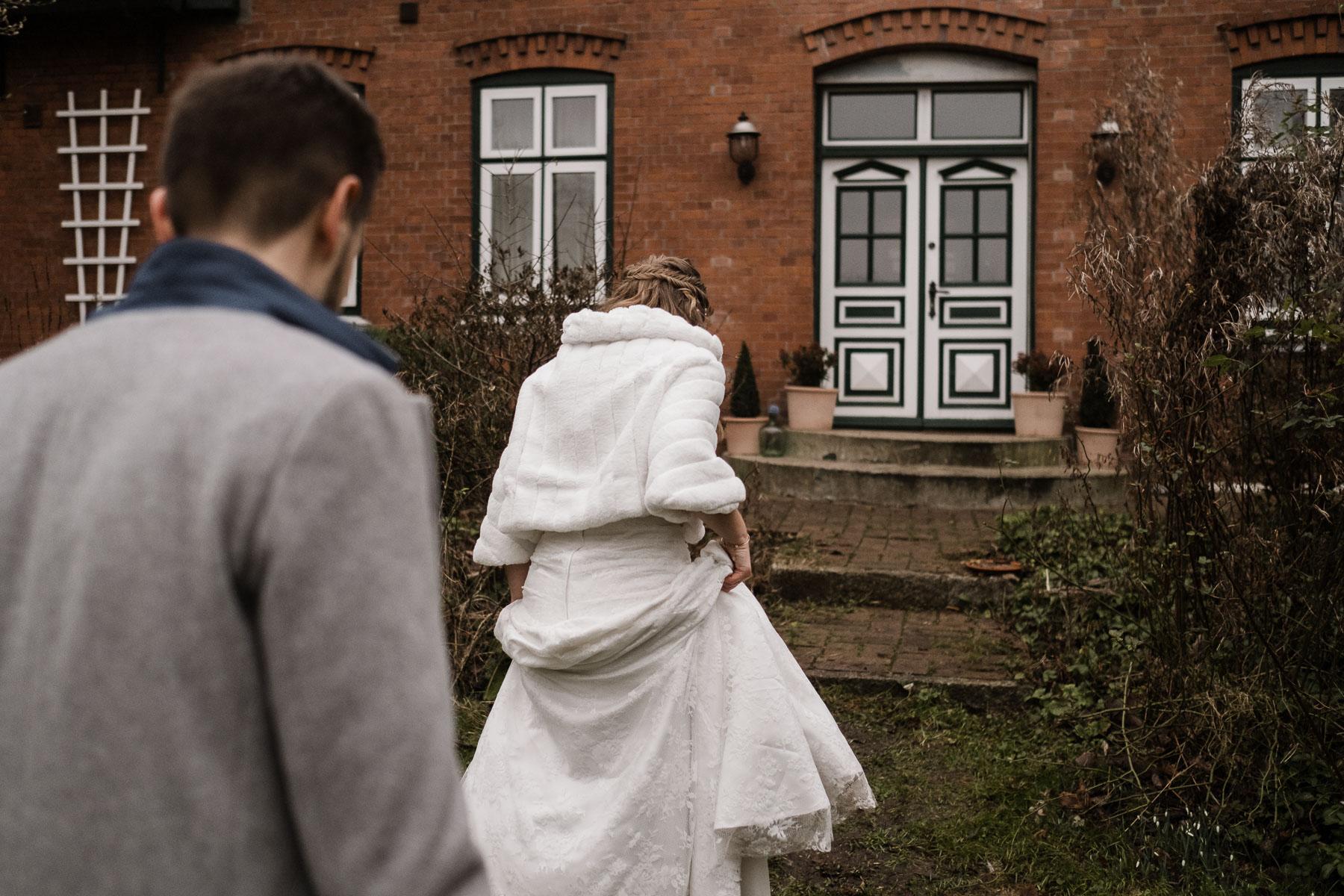 das Brautpaar geht in die Richtung eines Landhaus mit altn Holzfenstern und Holztüren, die Frau trägt ein langes Brautkleid mit einem Pelzumhang, der Bräutigam trägt über seinen Anzug einen Wollmantel, die Braut hält ihr Brautkleid hoch, sie steht vor den Stufen des Hauses, der Bräutigam geht hinter der Braut