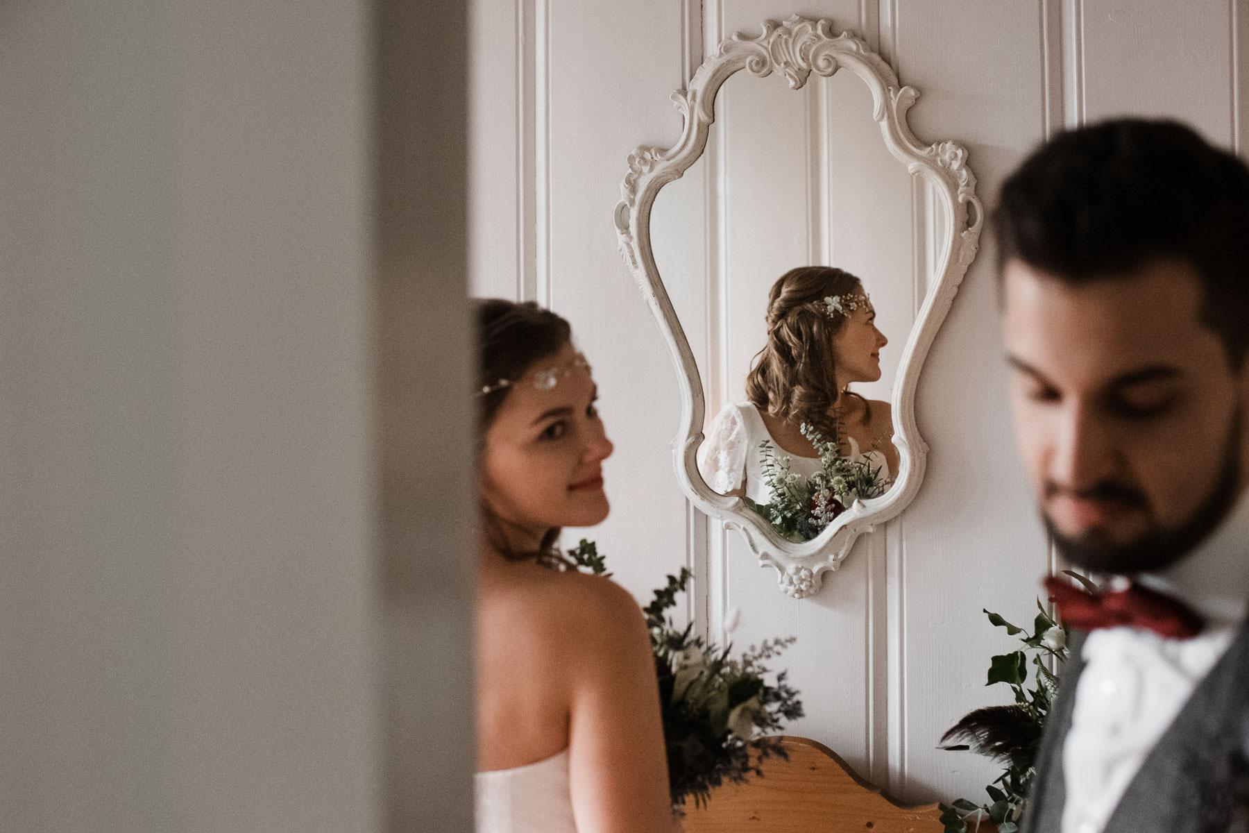 vor einer Wand, die weiß vertäfelt ist, steh die Braut, sie schaut nach hintn zu ihrem Bräutigam, in einem kleinen, weißen Spiegel spiegelt sich die Braut