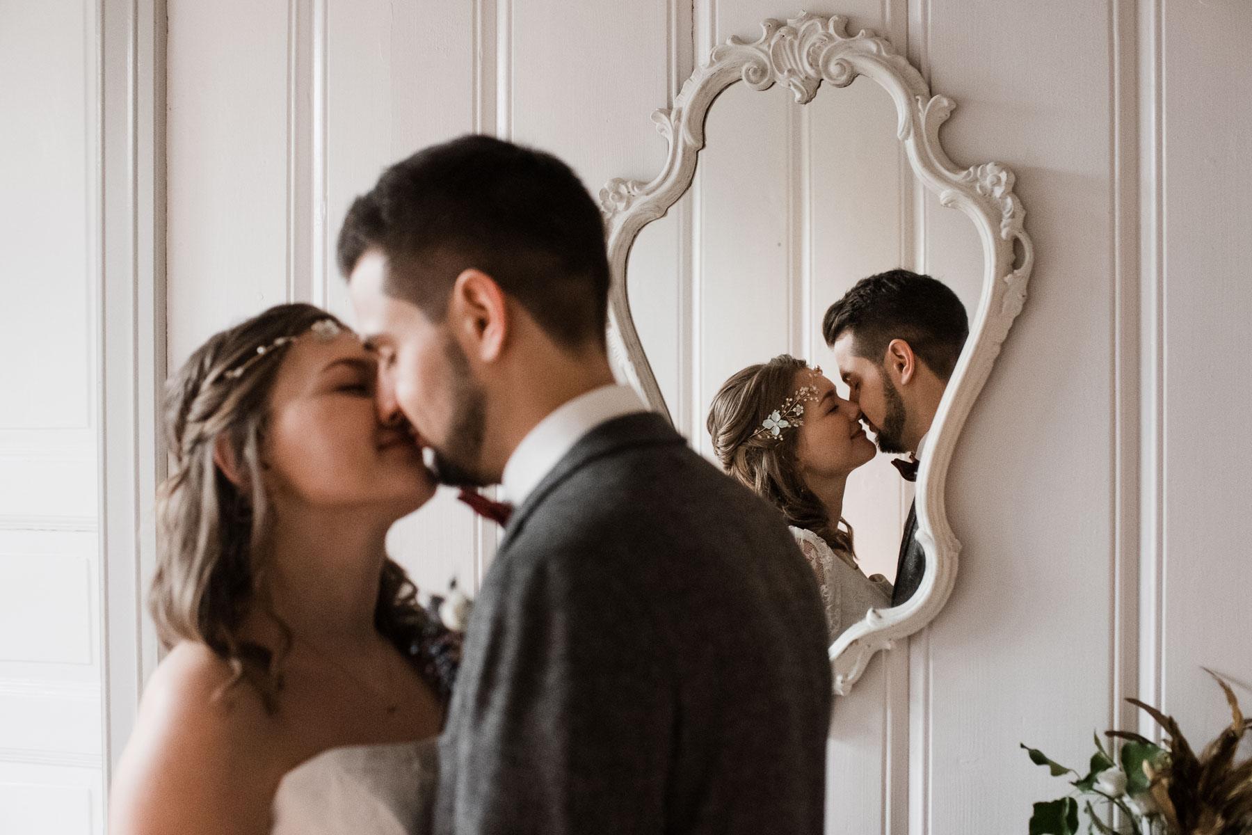 das Brautpaar küsst sich vor einer Wand, die weiß vertäfelt ist, in einem kleinen weißen Spiegel ist ihr Spiegelbild zu sehen