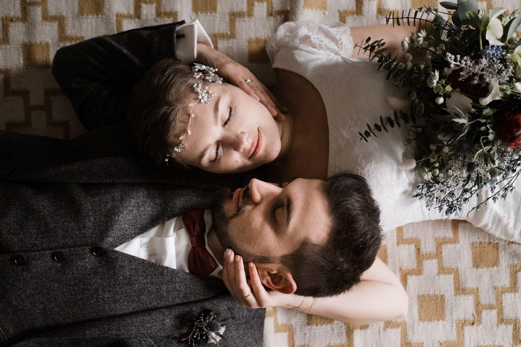 das Brautpaar liegt auf einem Retro-Teppich, nur ihre Köpfe berühren sich, der Bräutigam liegt mit dem Kopf auf den Arm der Braut, beide haben geschlossne Augen