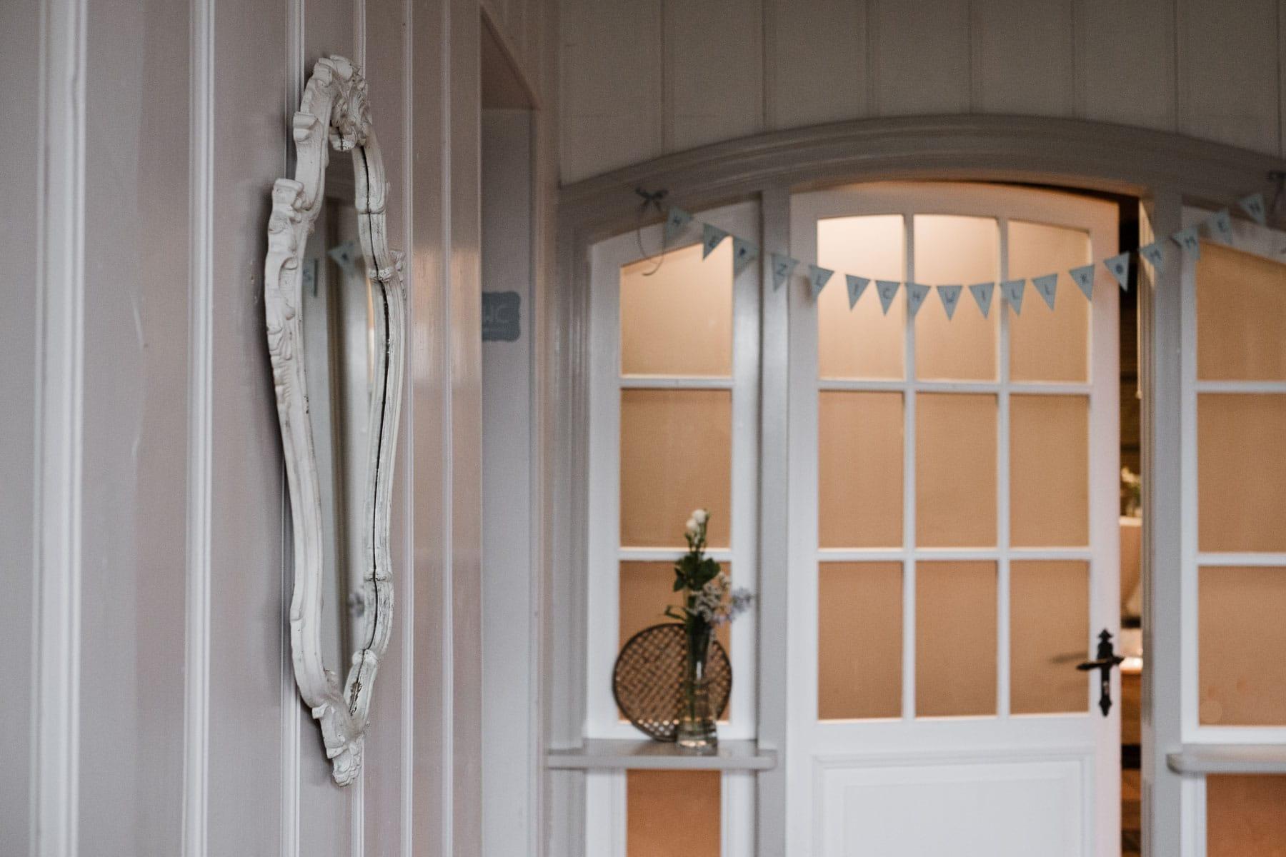 der Eingang eines Landhauses, eine große, weiße Bodentür, über der Tür hängt eine Wimpelkette