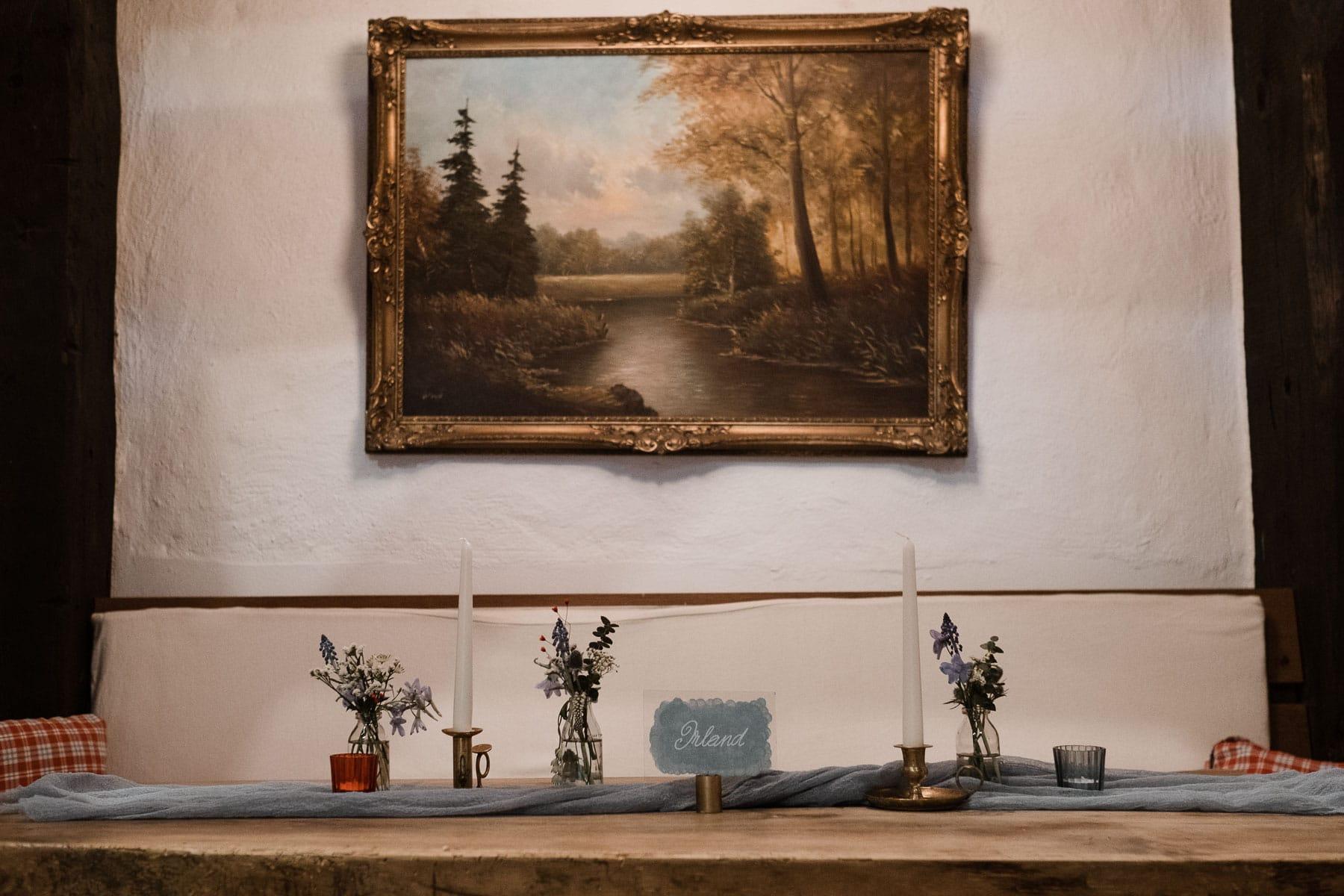 vor einer alten Wand in einem Landhaus hängt ein altes Bild mit einem Holzrahmen, davor steht ein Tisch, auf dem kleine Blumenvasen stehen und Kerzenständer