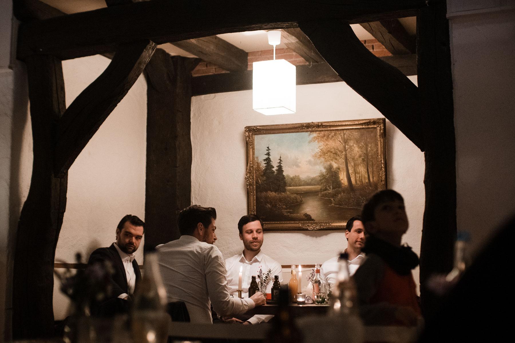 in einem Zimmer mit Holzgebälk sitzen 5 Männer um einen Tisch, hinter ihnen an der Wand hägt ein altes Bild, dass in einem goldenen Rahmen gefasst ist