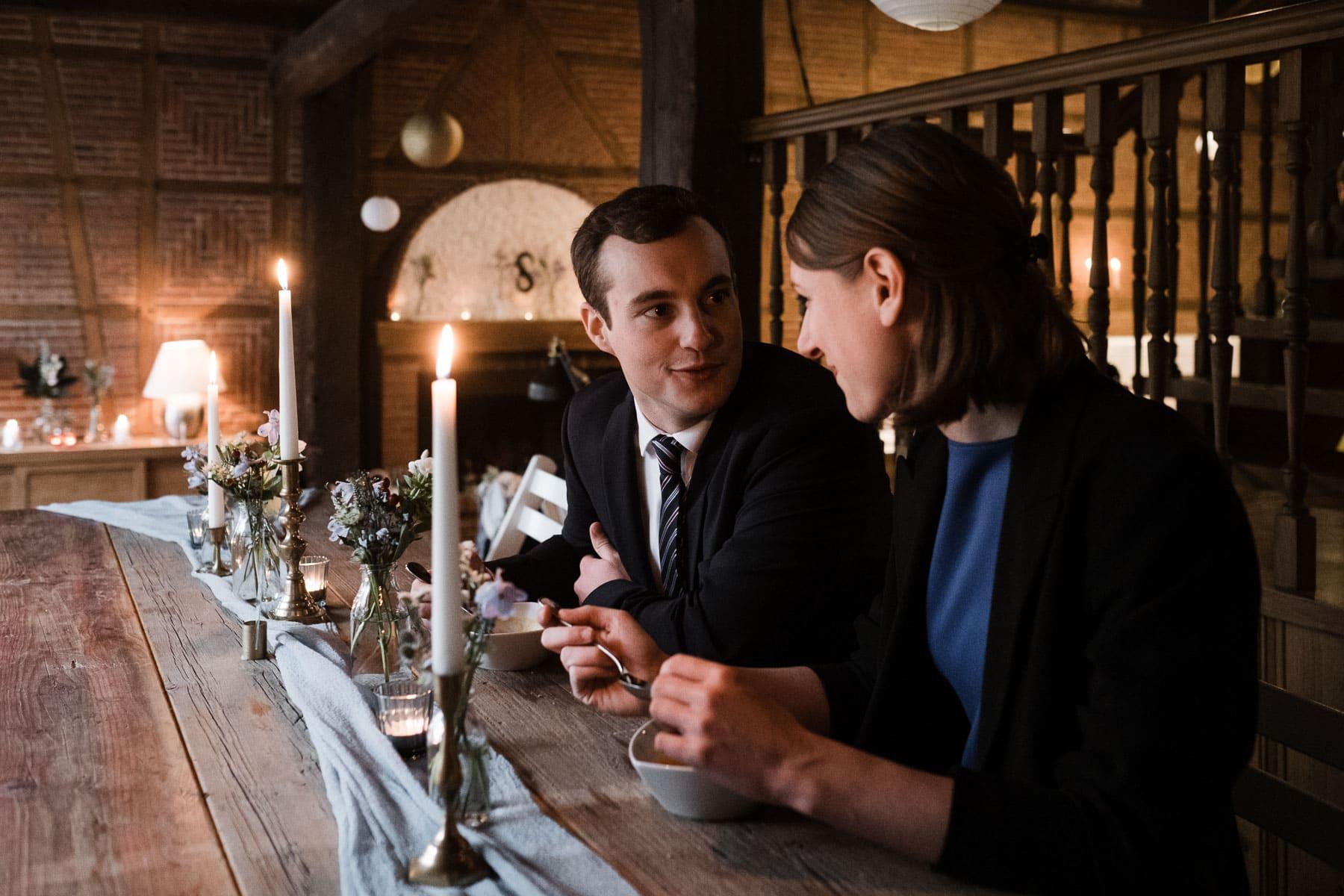 an einem langen Holztisch in einem Landhaus sitzen ein Mann und eine Frau, in der Mitte des Tisches stehen Blumenvasen und Kerzenständer, beide löffeln Kürbissuppe aus einer Schale, sie unterhalten sich dabei