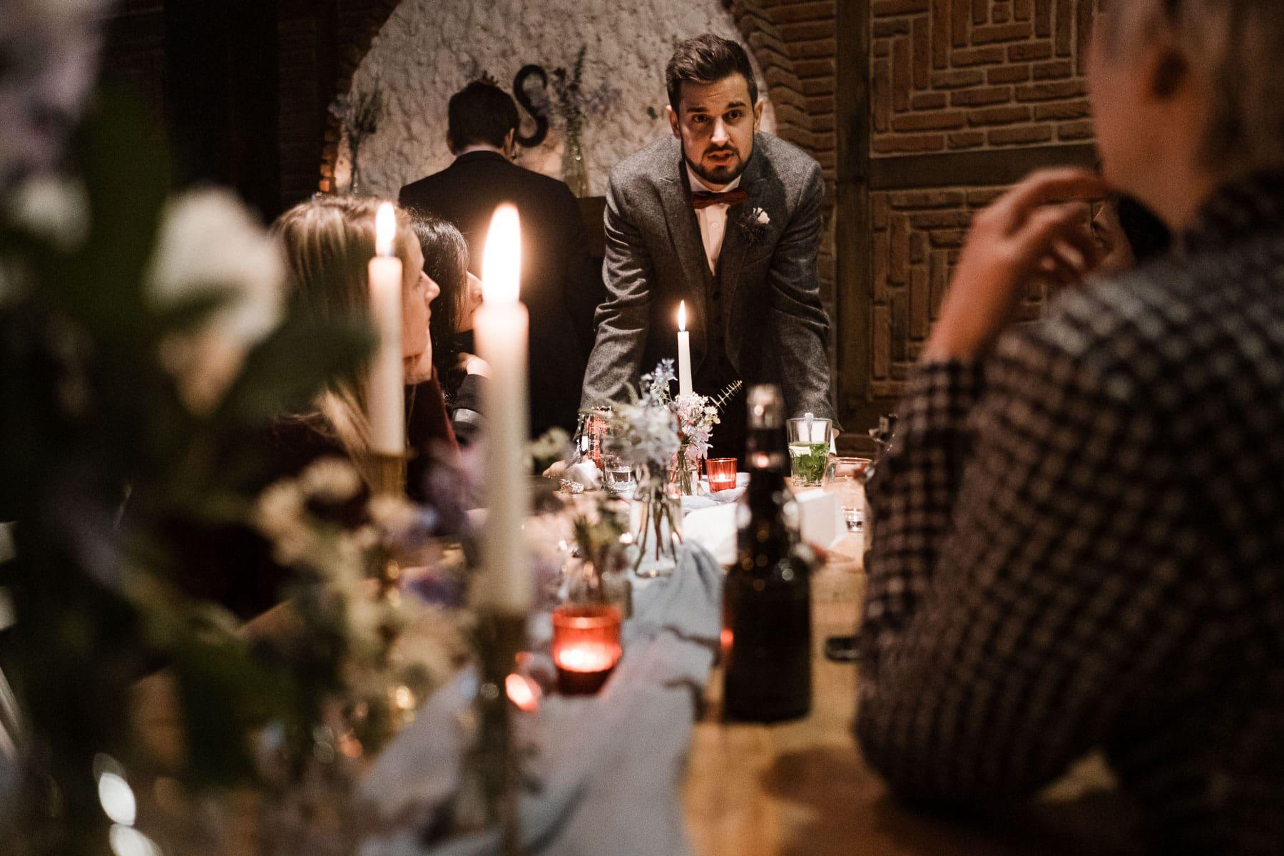 am Ende eines großen, langen Holztisches steht beugt sich der Bräutigam in Richtung der Gäste, die an dem Holztisch sitzen, auf dem Holztisch stehen Kerzenständer und Blumenvasen, sowie Getränkeflaschen