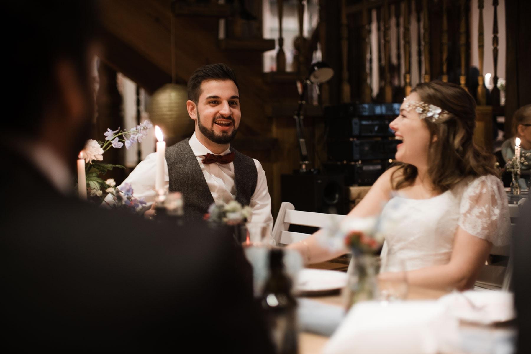 das Brautpaar sitzt an einem Tich in einem Zimmer in einem Landhaus, sie schauen sich an und lachen