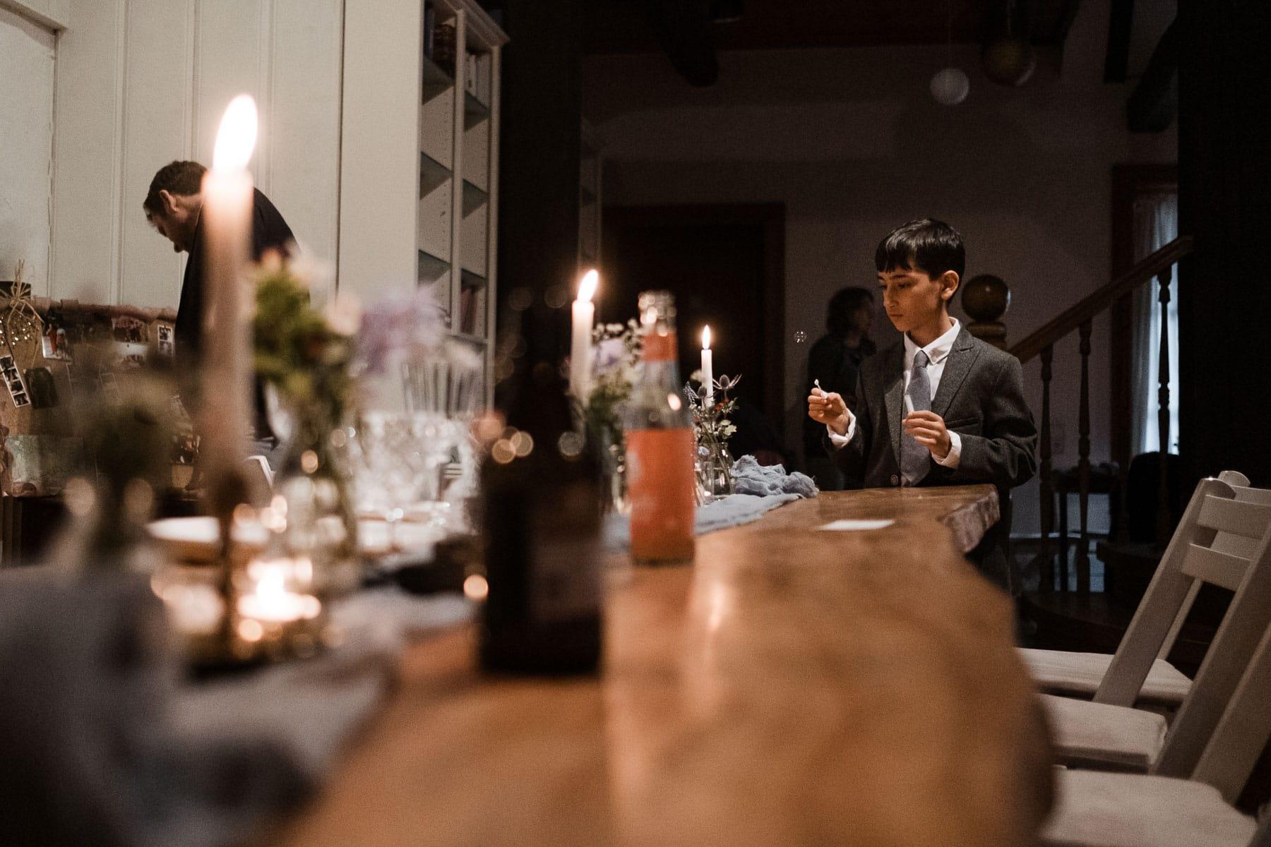 ein kleiner Junge steht am Ende einer großen Holztafel, auf dem langen Tisch stehen Kerzenständer und Blumenvasen
