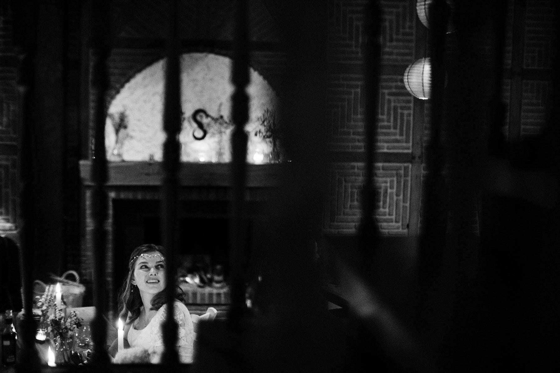 hinter einem Treppengeländer ist die Braut zu sehen, sie sitzt auf einem Stuhl an einer Holztafel, hinter ihr ist ein großes Milchglasfenster mit einer Gravur