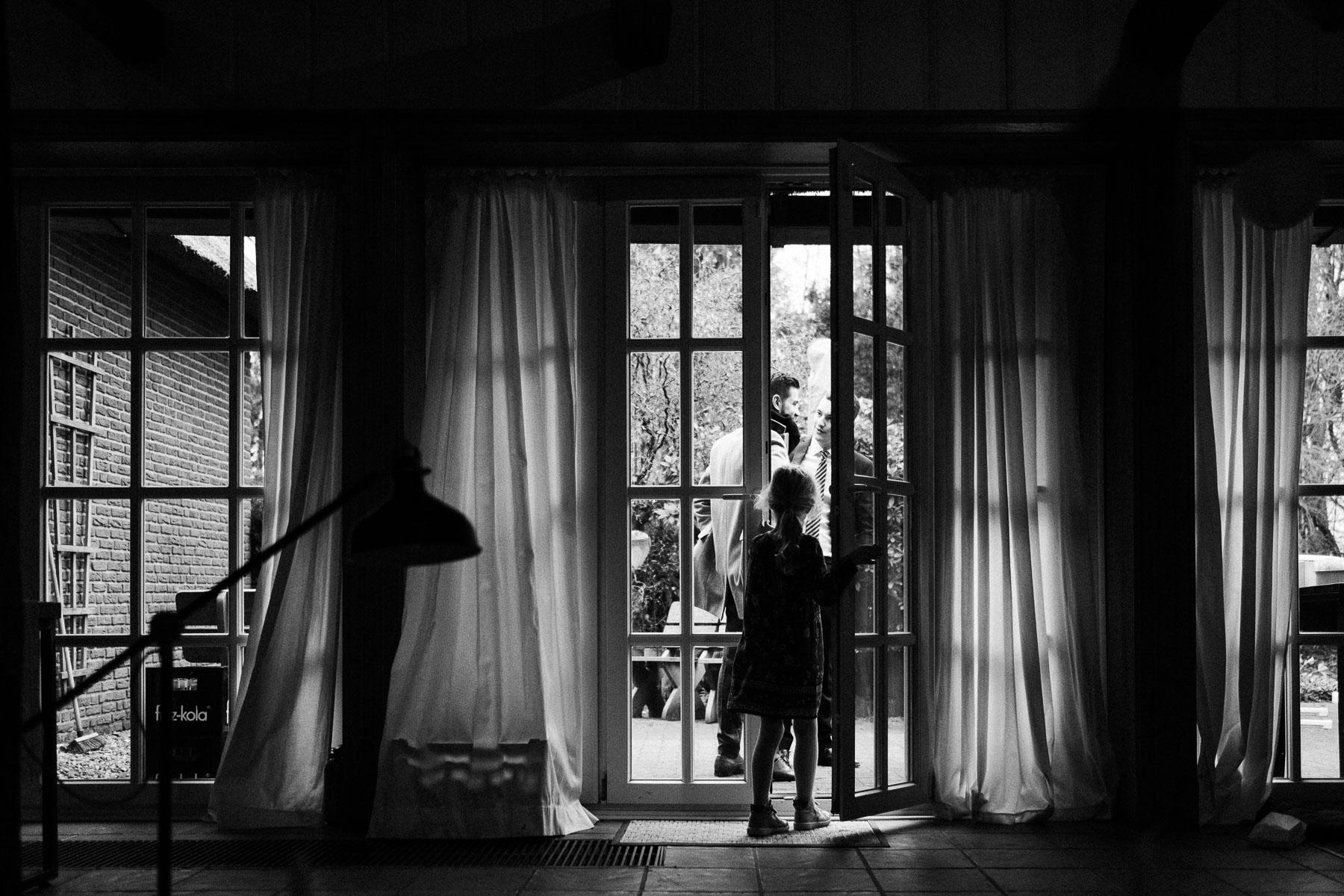 vor einem bodenlangem Sprossenfenster in einem Landhaus steht ein kleines Mädchen, eine Tür des Fenster steht offen, vor den Fenstern hängen helle, leichte Gardinen