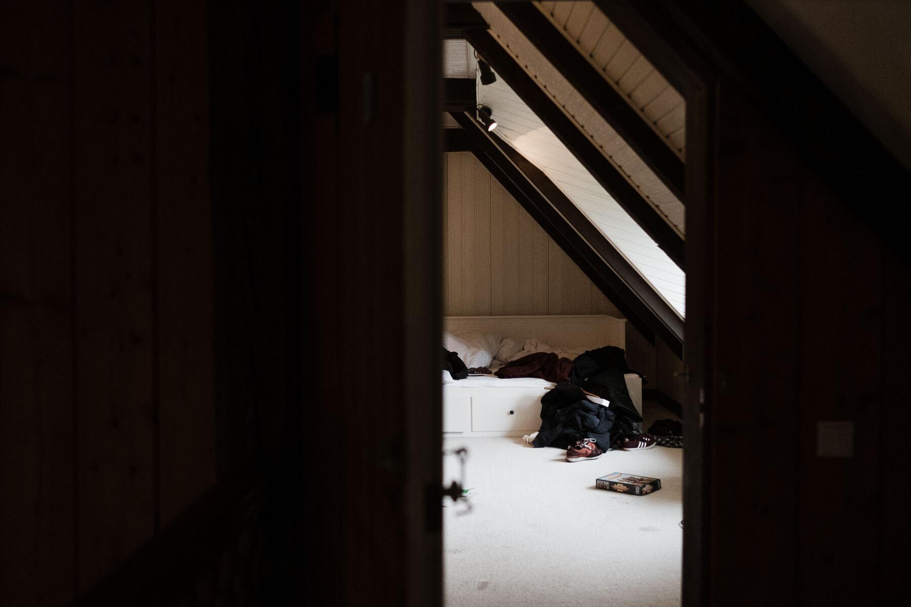 in einem Dachzimmer steht ein Bett, auf dem viele Kleidugsstücke liegen