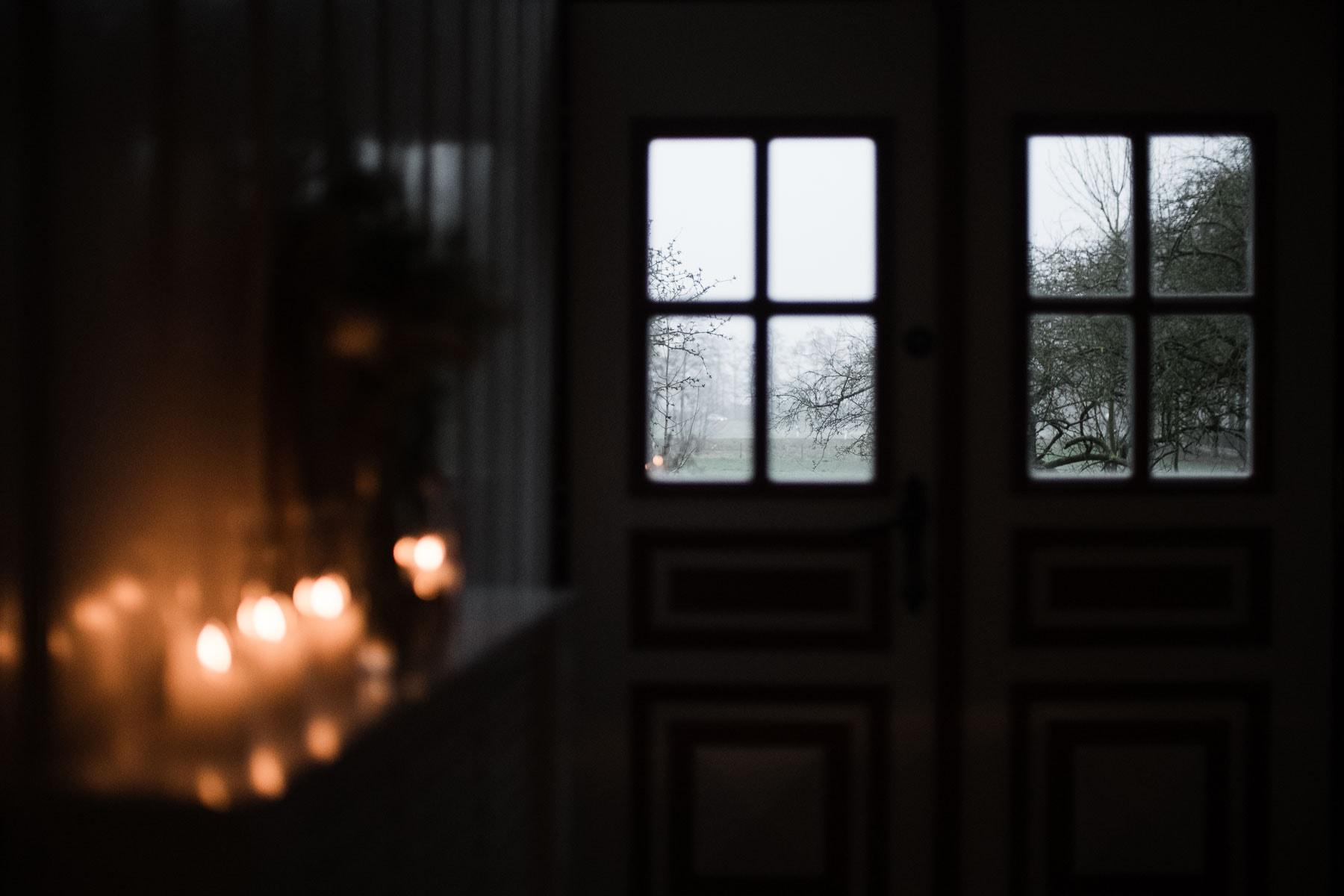 im Flur eines Landhauses hängt ein Regal an der Wand, auf dem Kerzen stehen, im HIntergrund ist eine Tür mit Sprossenfenstern