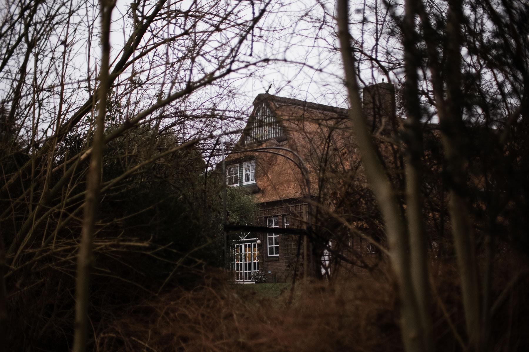 ein Landhaus, dass von kahlen Bämen umgeben ist, es hat Sprossenfenster