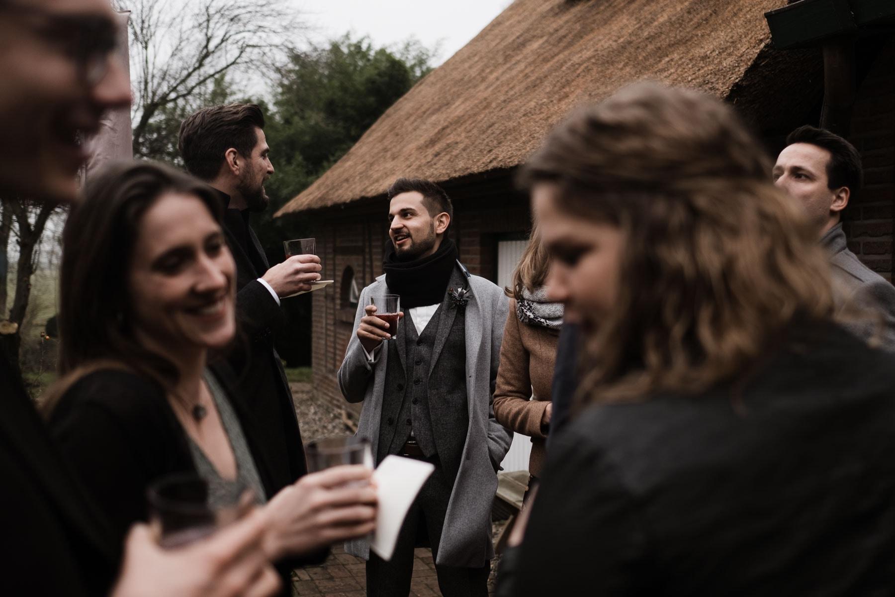 draußen vor einem Landhaus steht ein Bräutigam mit seinen Gästen, sie alle haben Becher mit Punsch in den Händen, sie unterhalten sich