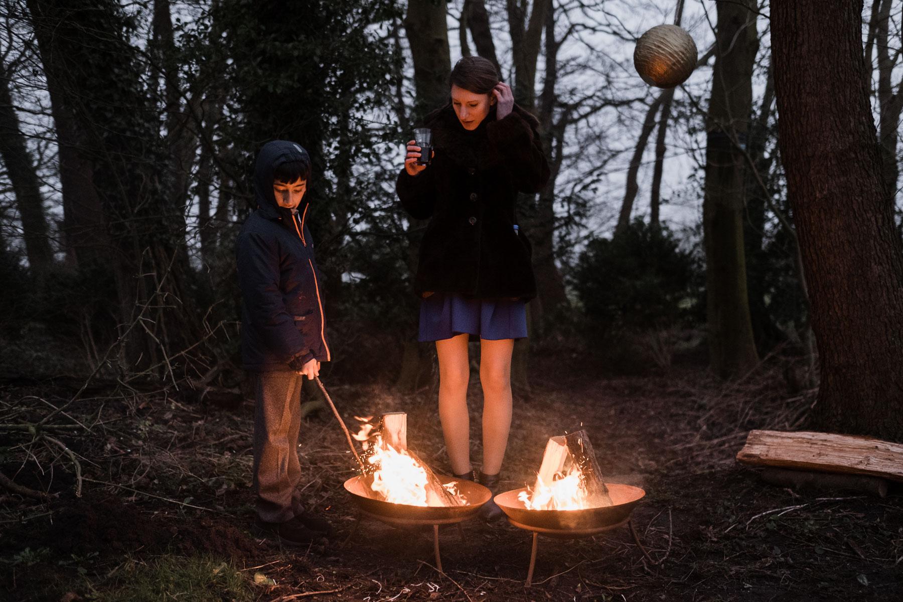 vo einer kahlen Baumkulisse stehen 2 runde Feuerschalen, hinter den Feuerschalen steht ein Junge und eine Frau, der Junge hält einen Stock in die Feuerschale